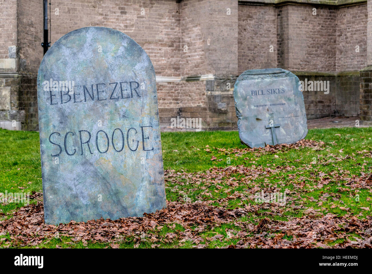 Fake headstones of Ebenezer Scrooge and Bill Sikes in the churchyard of Saint Nicholas Church at the Deventer Dickens - Stock Image