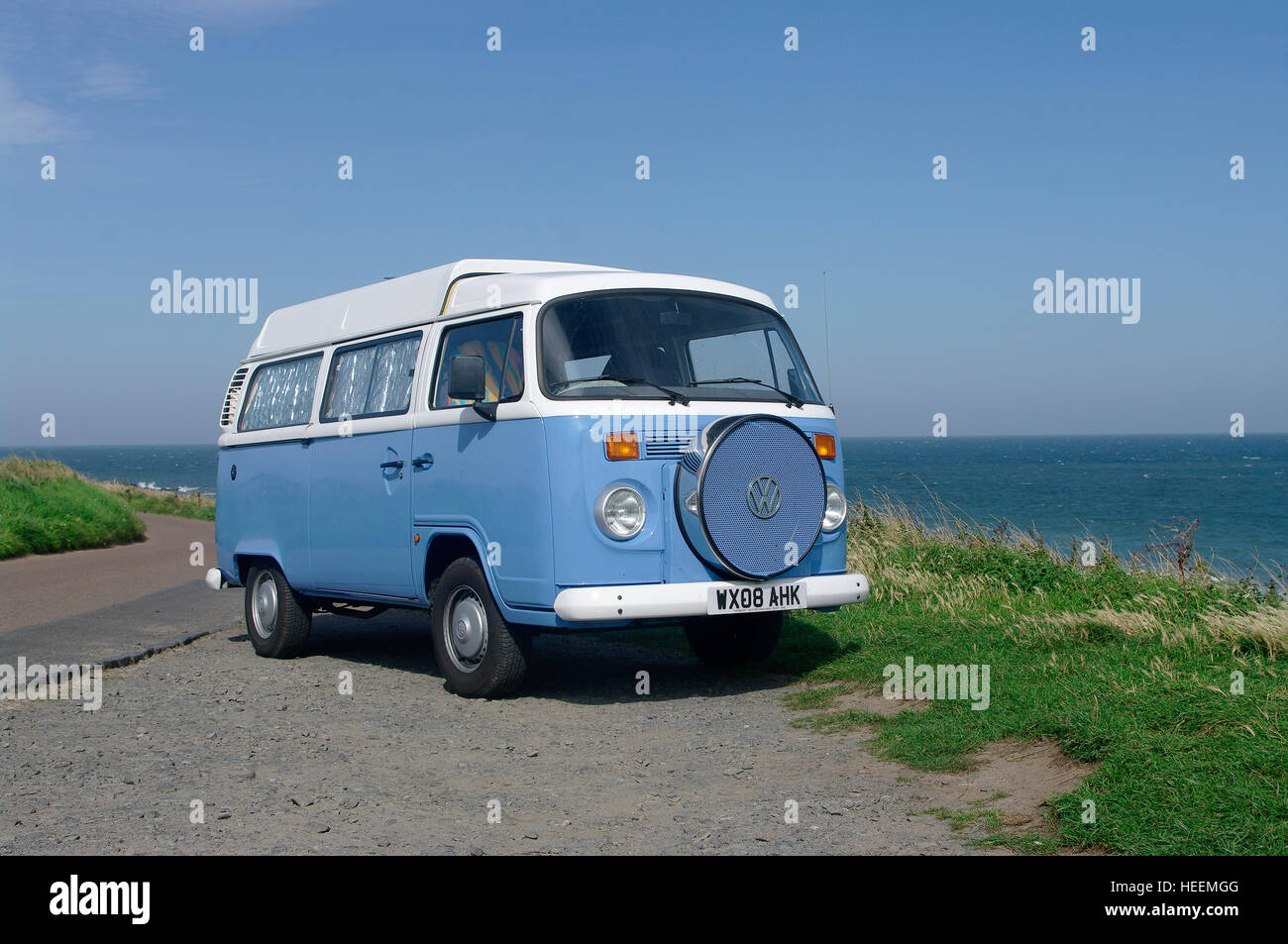 VW Campervan on the coast at Bamburgh,Northumberland - Stock Image