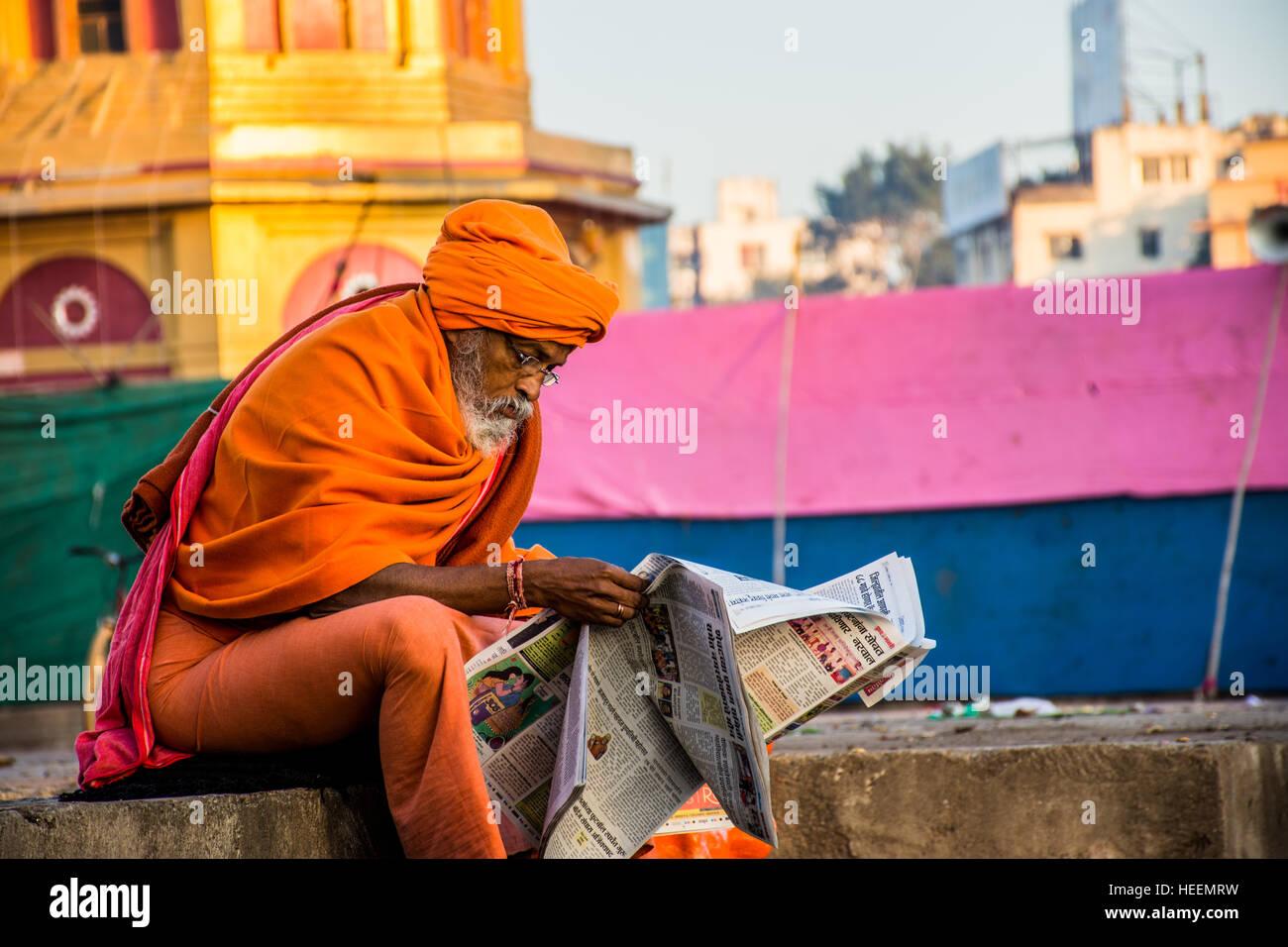 A sadhu reading newspaper. - Stock Image
