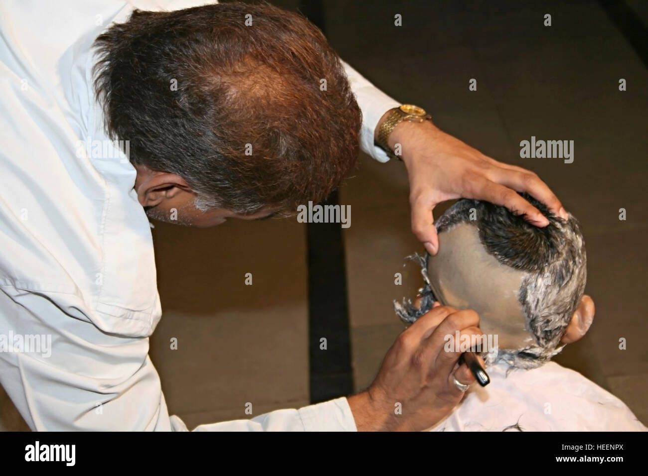 Getting a hair-cut for threading ceremony, a typical Hindu ritual