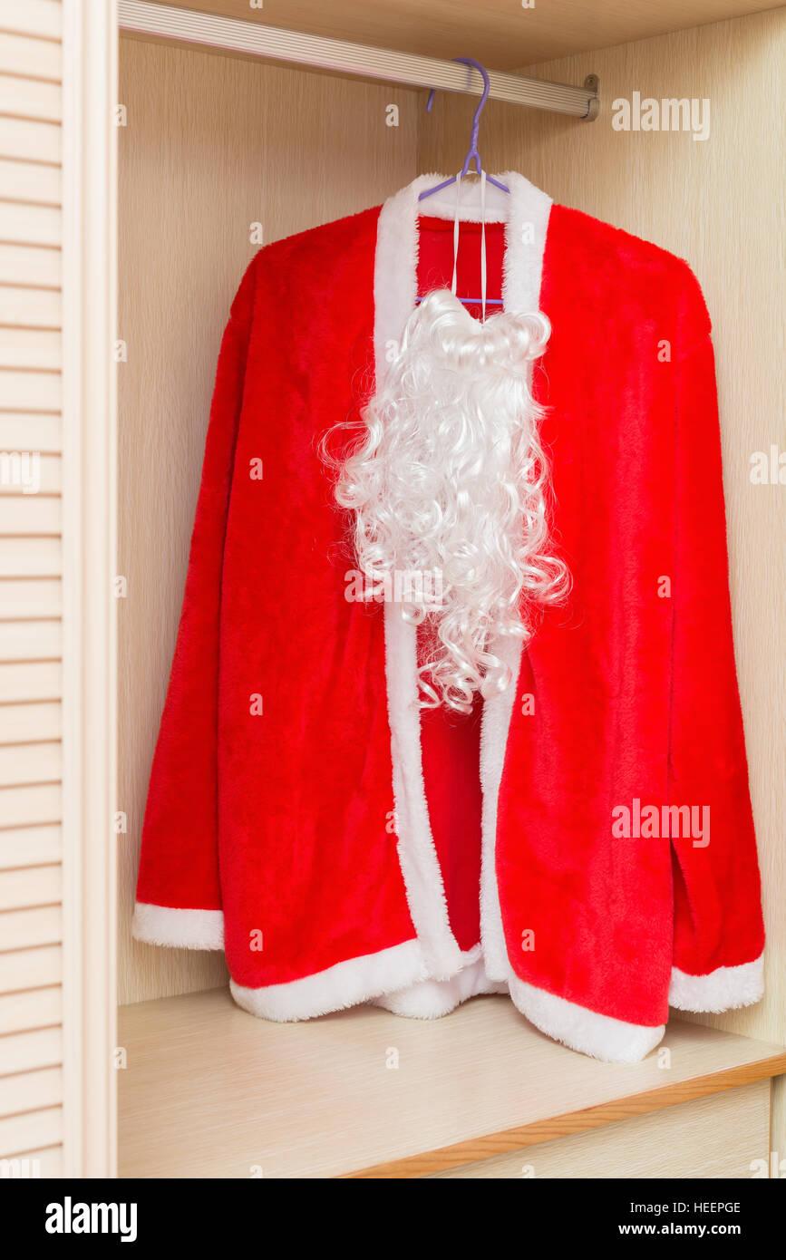 santa claus coat and beard hanging in a wardrobe stock image - Santa Claus Coat