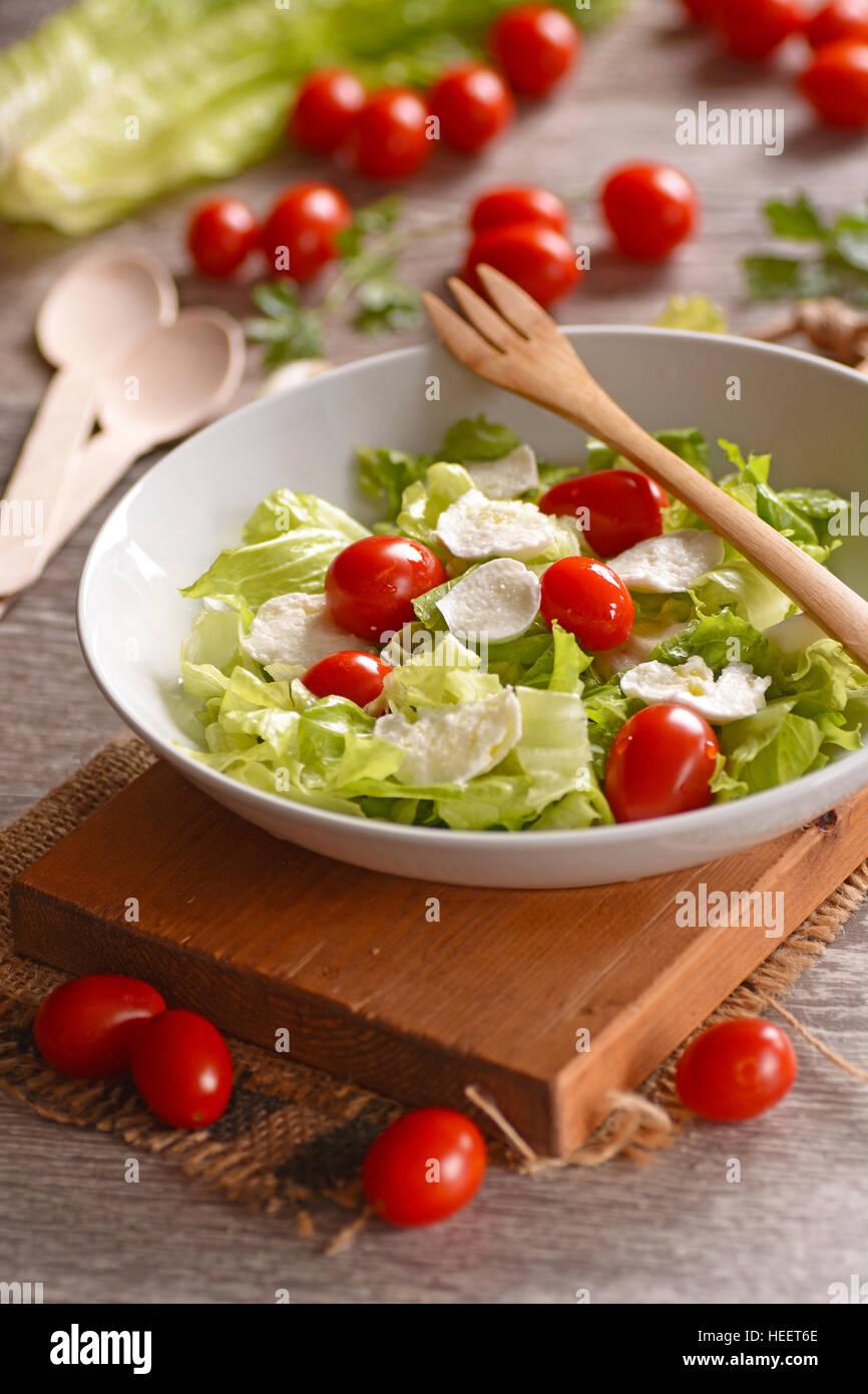 lettuce salad, mozzarella and tomato - Traditional Italian recipe - Stock Image