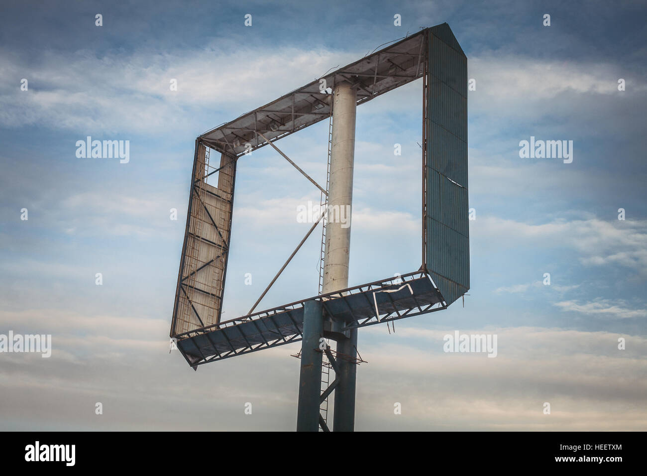 Empty billboard against partly cloudy blue sky. - Stock Image