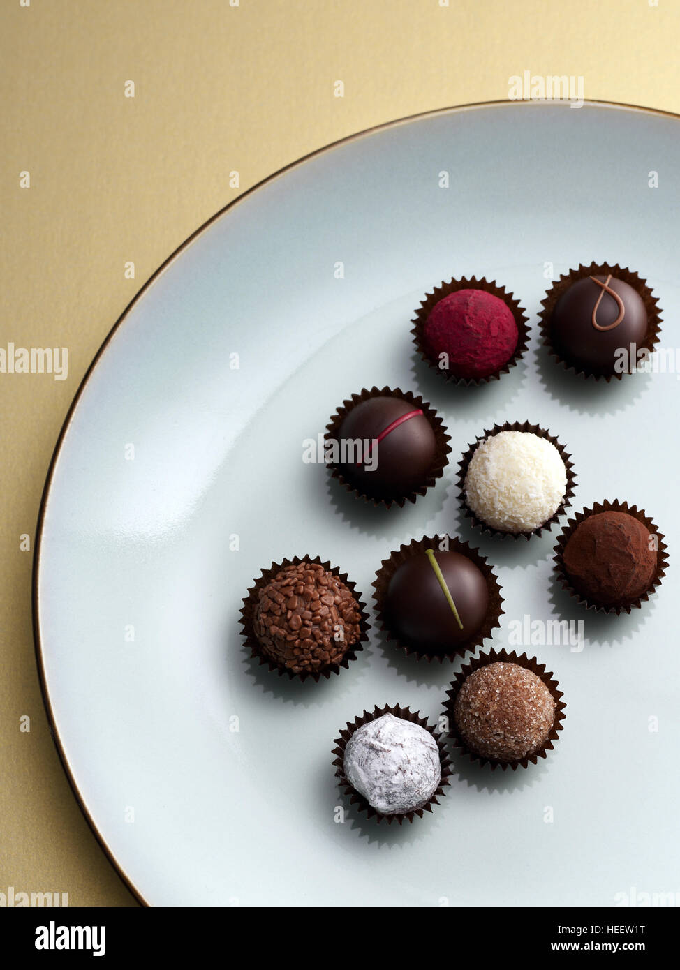 Chocolate pralines and truffles on blue plate and gold background - Stock Image