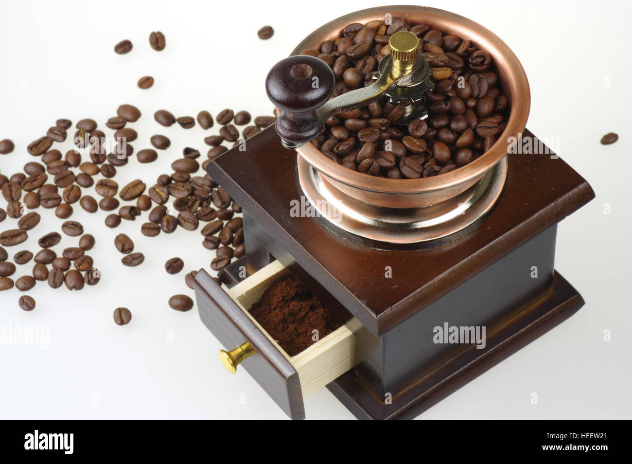 Old-style manual coffee grinder on the white background. Around the mill are scattered coffee beans. - Stock Image