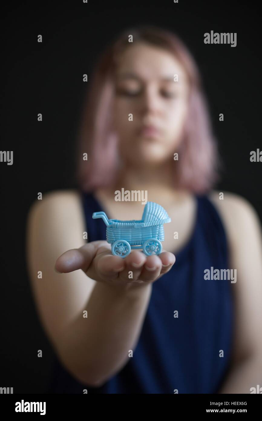 A teen girl holding a miniature baby carriage in the palm of her hand. - Stock Image