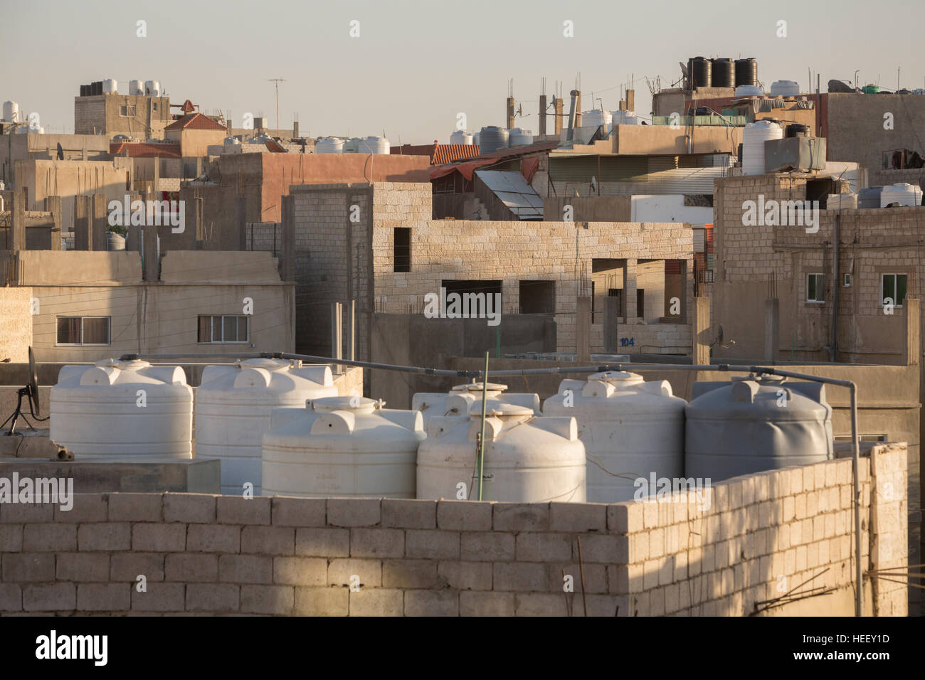 Water storage tanks sit on a rooftop in Zarqa, Jordan. - Stock Image
