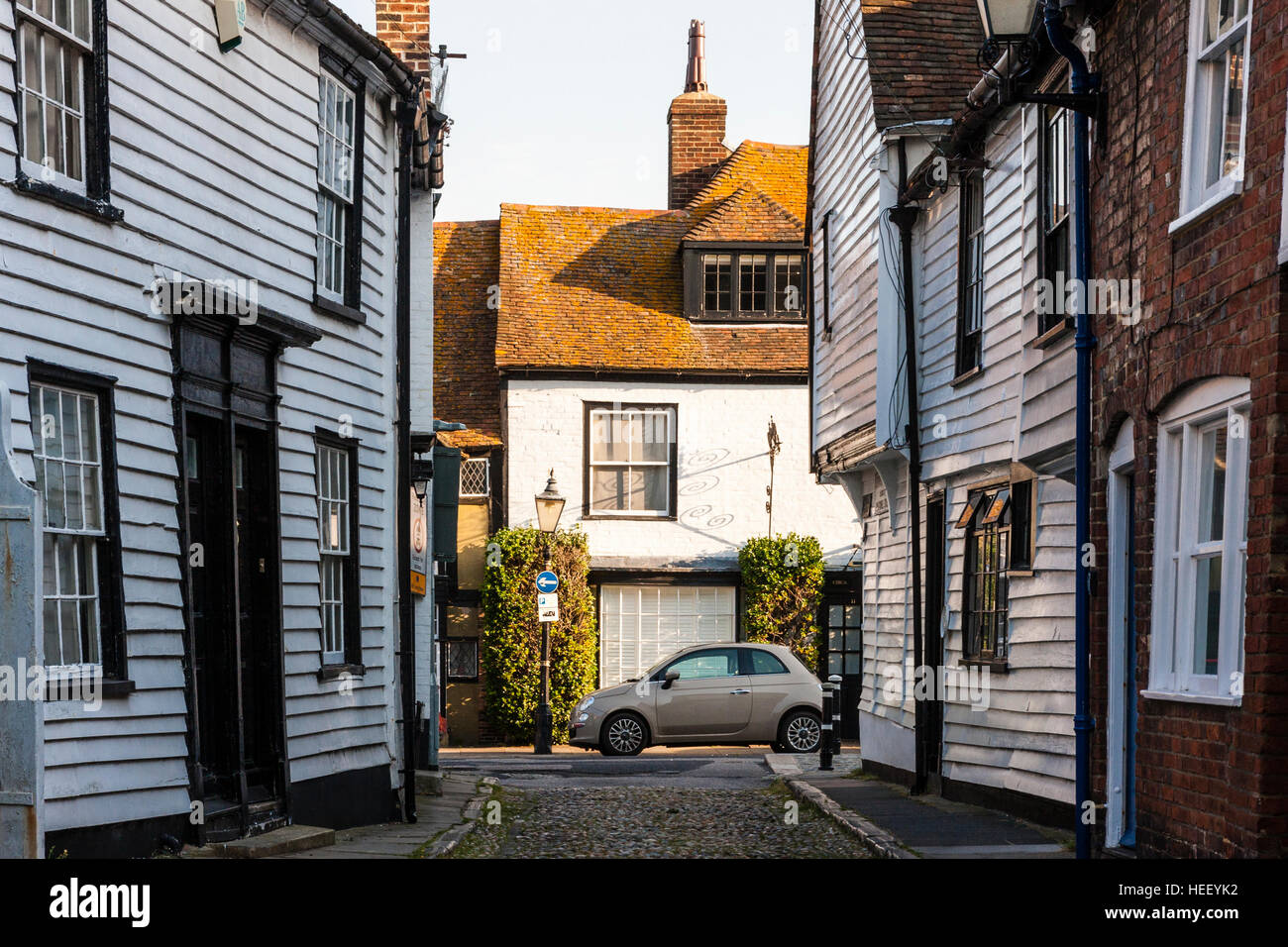 England, Rye. House, parked car outside, seen at end of street with white wooden weatherboarded 18th century houses - Stock Image