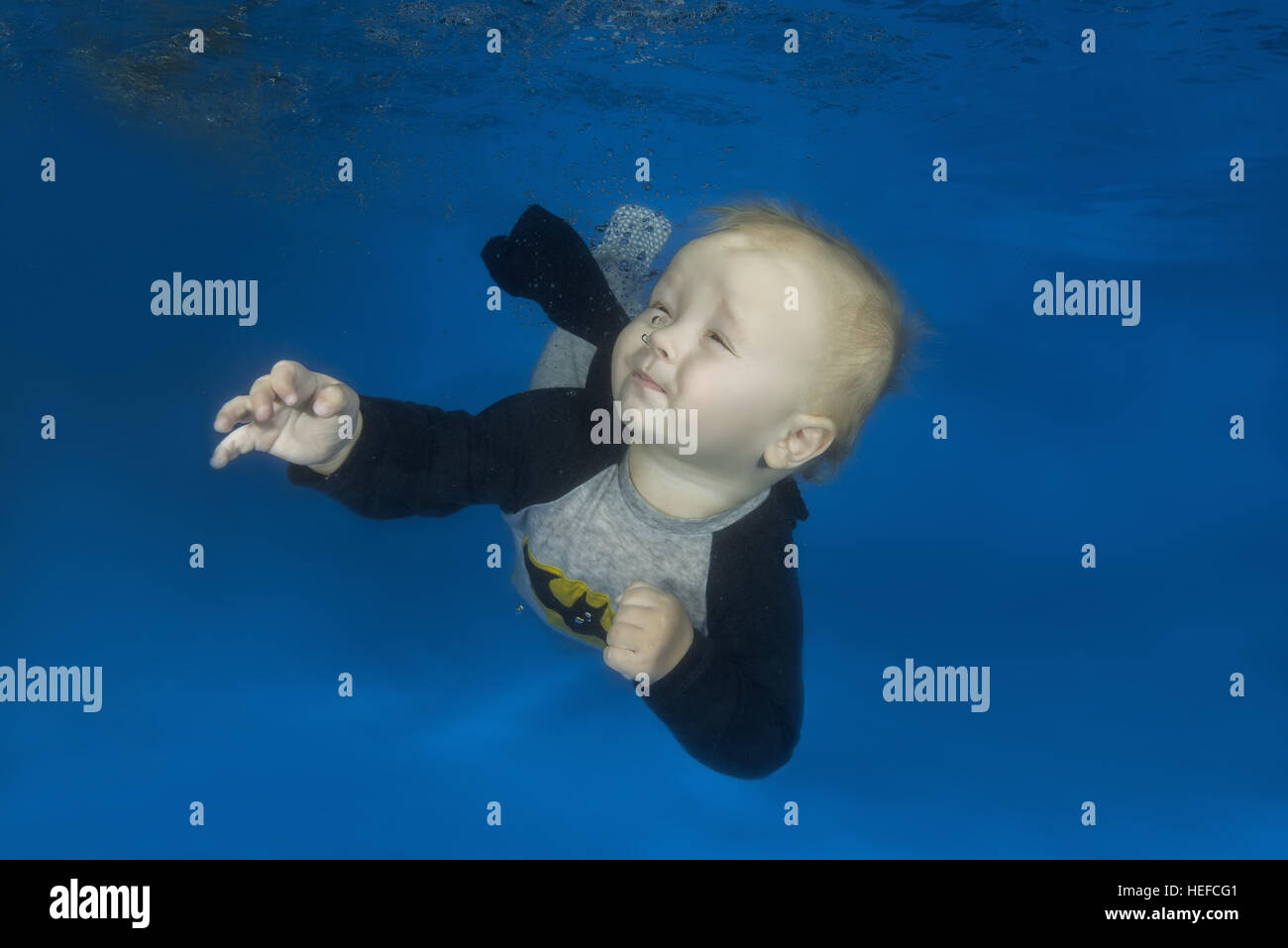 6da07e46bce37 Little boy in a Batman costume posing under the water in the pool ...