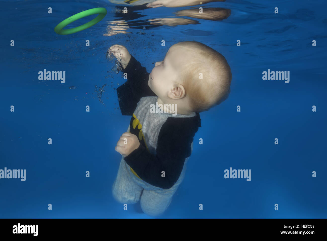 c99e5610e2851 Little boy in a Batman costume posing under the water in the pool - Stock  Image