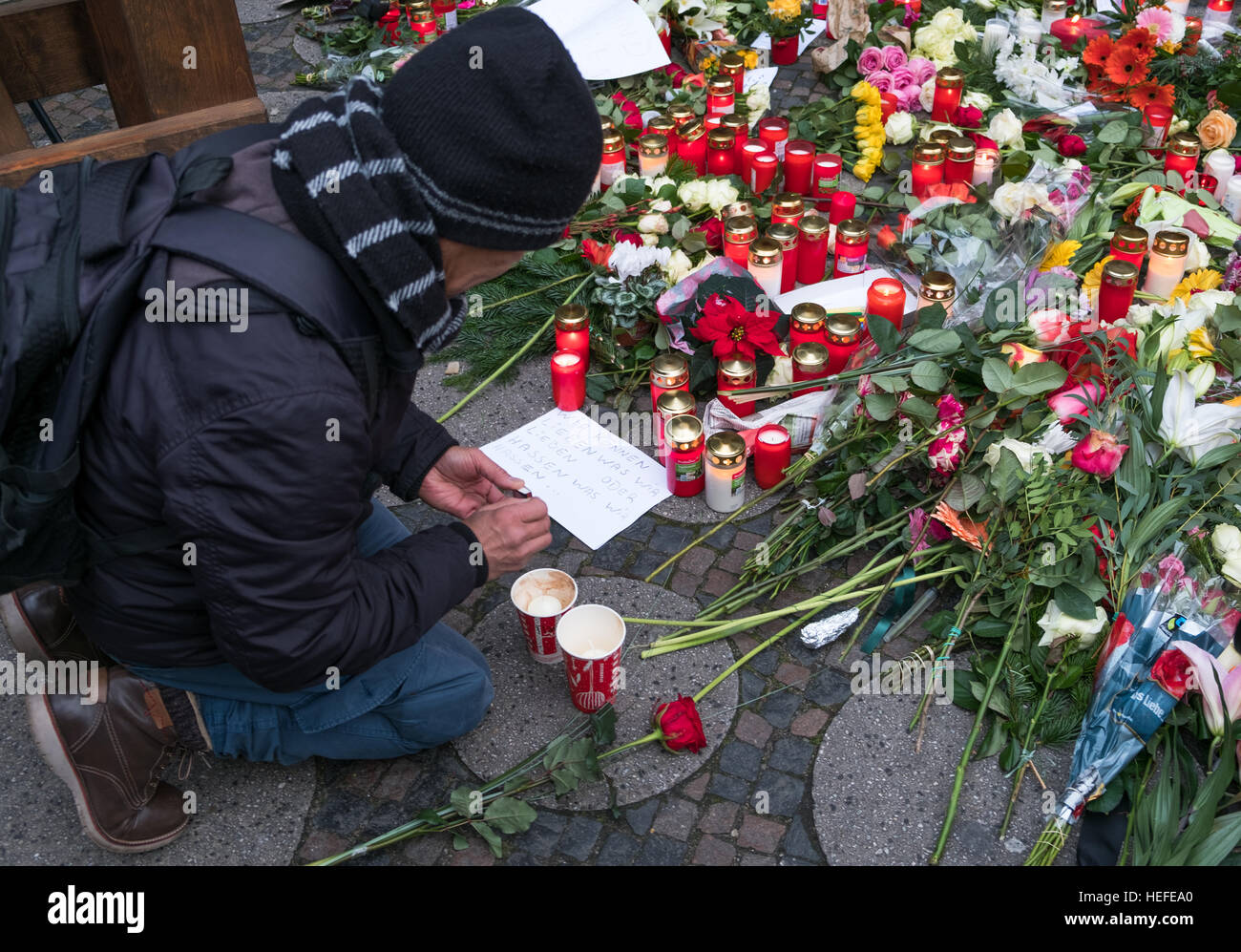 Death flowers candle stock photos death flowers candle stock man put candle and flowers at the christmas market in berlin the day after the izmirmasajfo