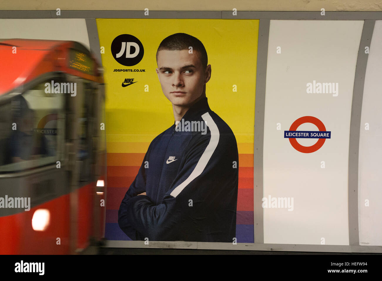 A JD Sports advert on Leicester Square tube station as a train arrives - Stock Image