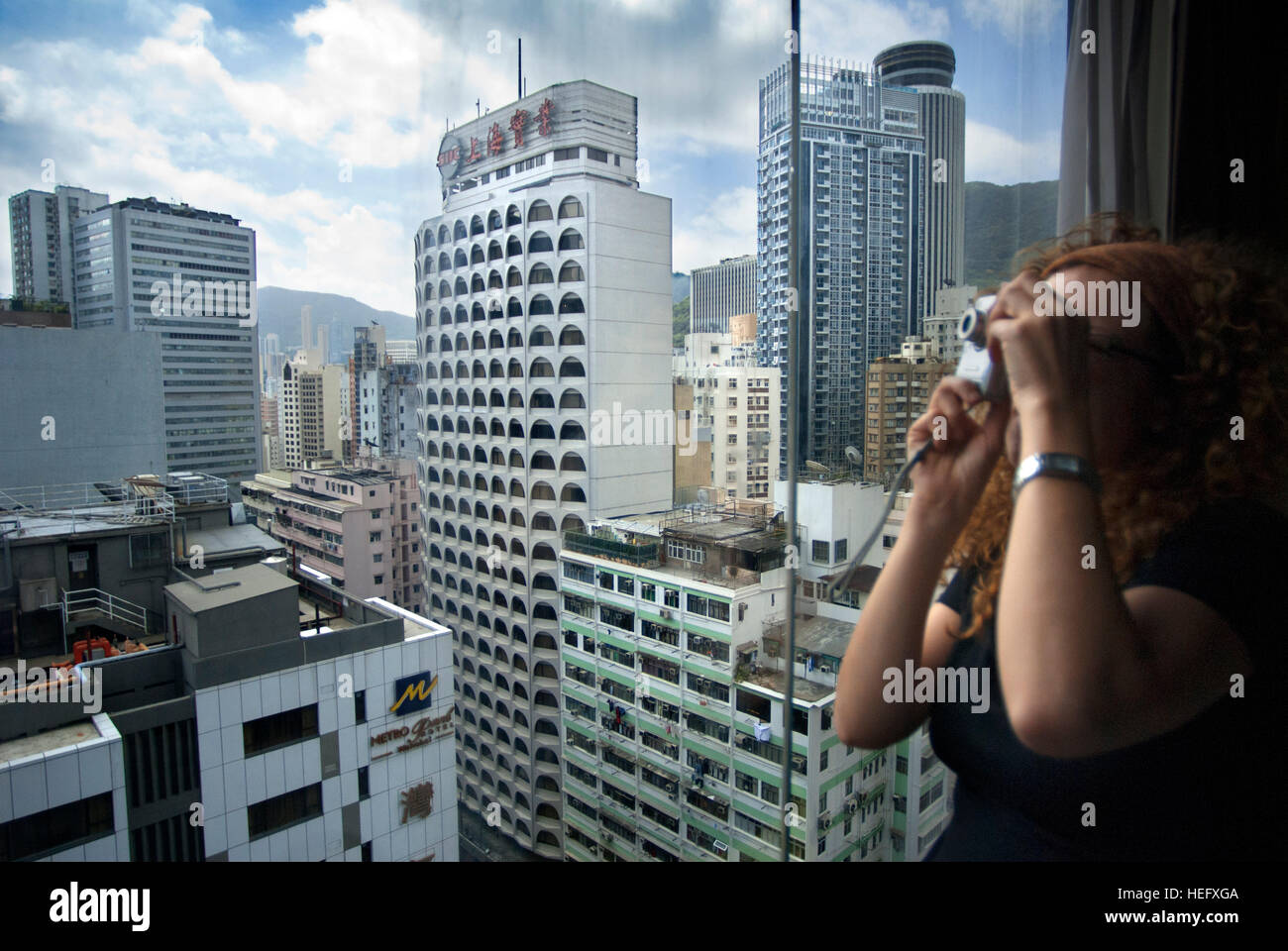 Woman takes pictures at Financial centre of Hong Kong with his moderm skyscrapers. Central Business District, Hong - Stock Image