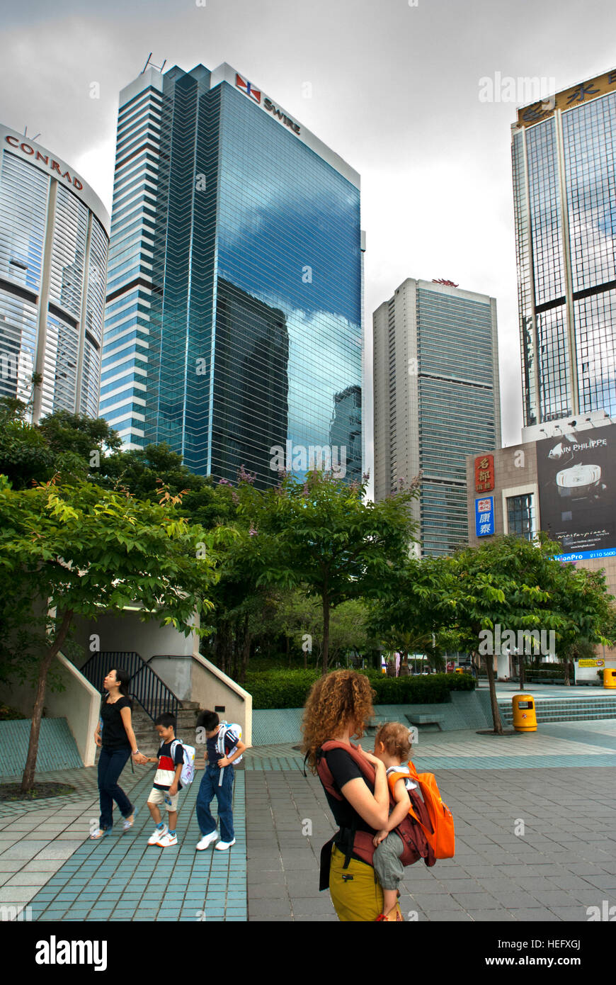 Mother with her child in the Financial centre of Hong Kong with his moderm skyscrapers. Central Business District, - Stock Image