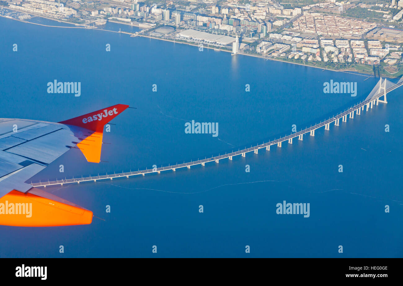 Airbus A320 operated by EasyJet (flight number EZY 7603) flights over Lisbon city. Aerial view through the airplane - Stock Image