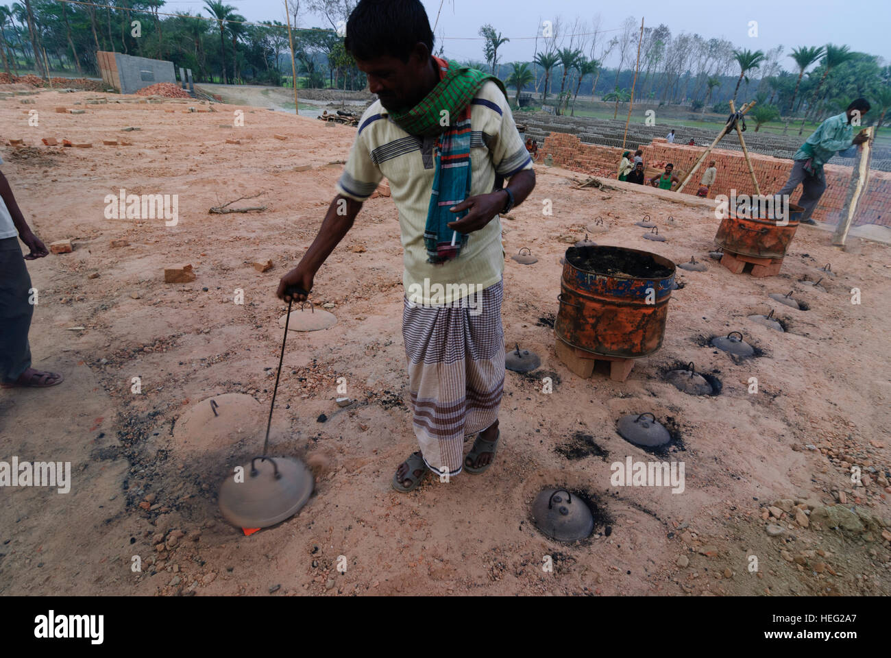 Noapra: Brickwork in the form of a ring furnace; The worker opens a hole to control the fire, bricks, Khulna Division, - Stock Image