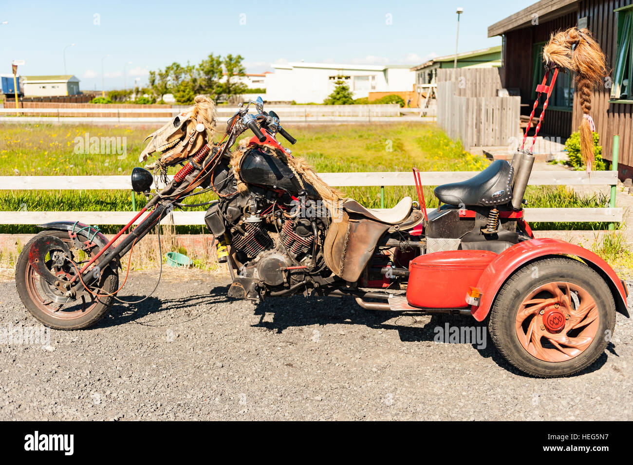 A custom-made three-wheeled motorcycle / chopper adorned with a horse skull and wigs. - Stock Image