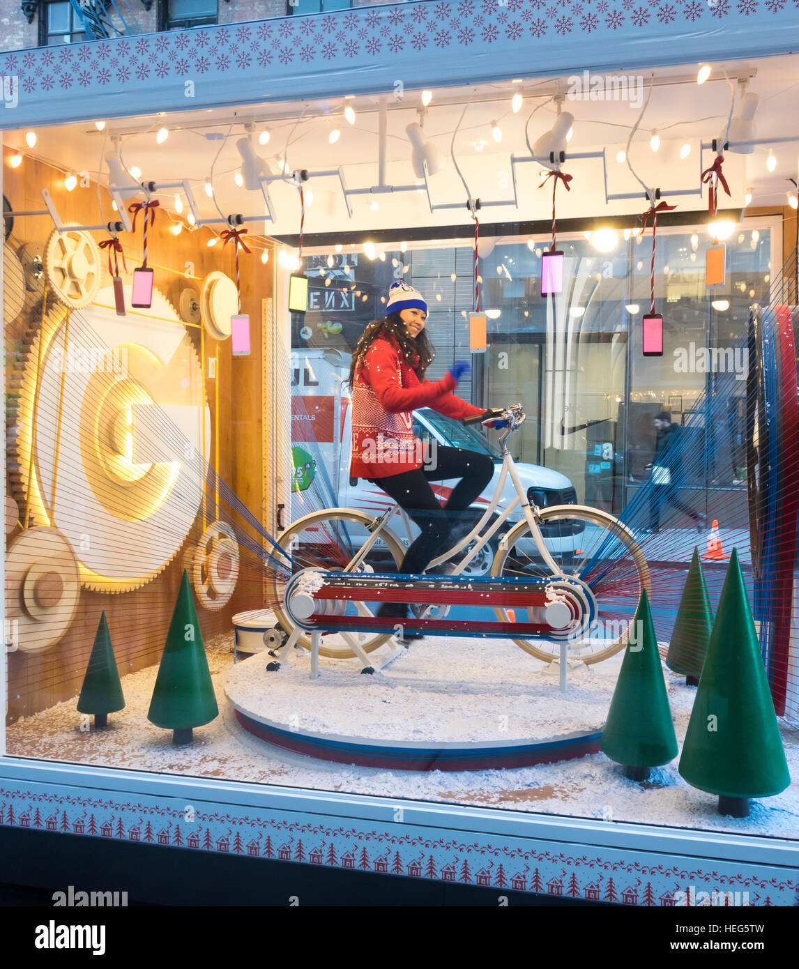 Young Asian woman on a stationary bike in a Google pop-up in Soho in New York City - Stock Image