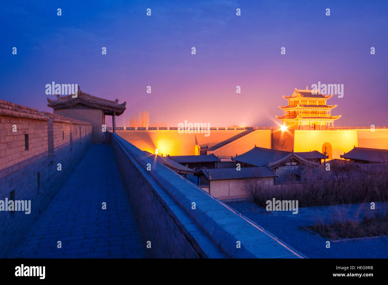 Jiayuguan fort illuminated at twilight at the western boundary of the Great Wall of China. The pass was a key waypoint - Stock Image