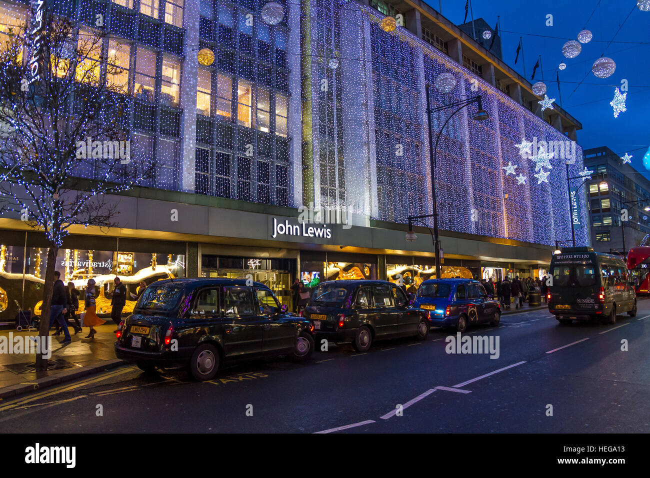 Line of Black London Taxis outside John Lewis Department Store at Christmas Time waiting to pick up Christmas Shoppers,Oxford - Stock Image