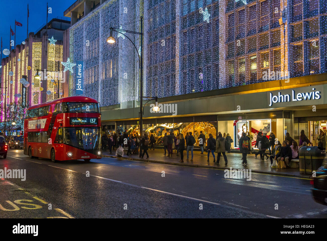 John Lewis Department store on a busy Oxford St bustling with Christmas shoppers at Christmas with The Oxford St - Stock Image