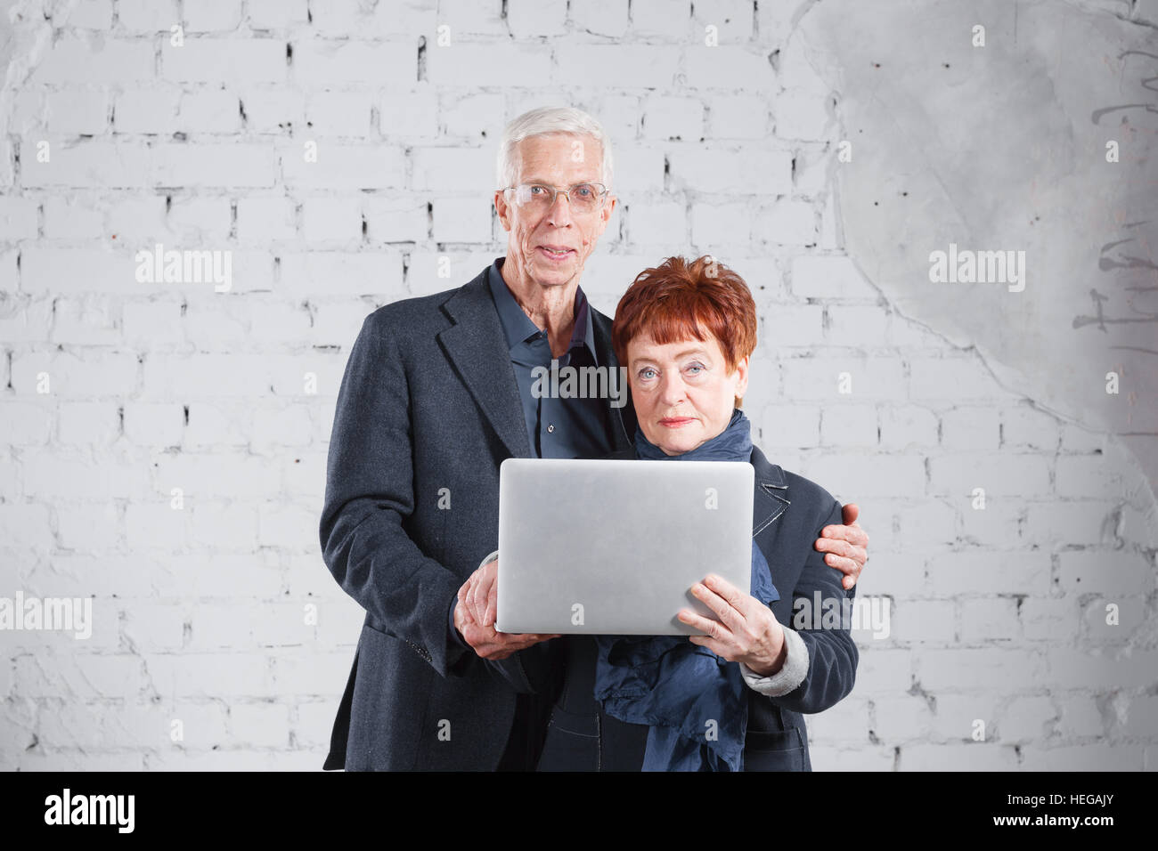 Old people hold a laptop and communicate through the Internet. Happy smiling grandpa grandma couple standing cuddling - Stock Image