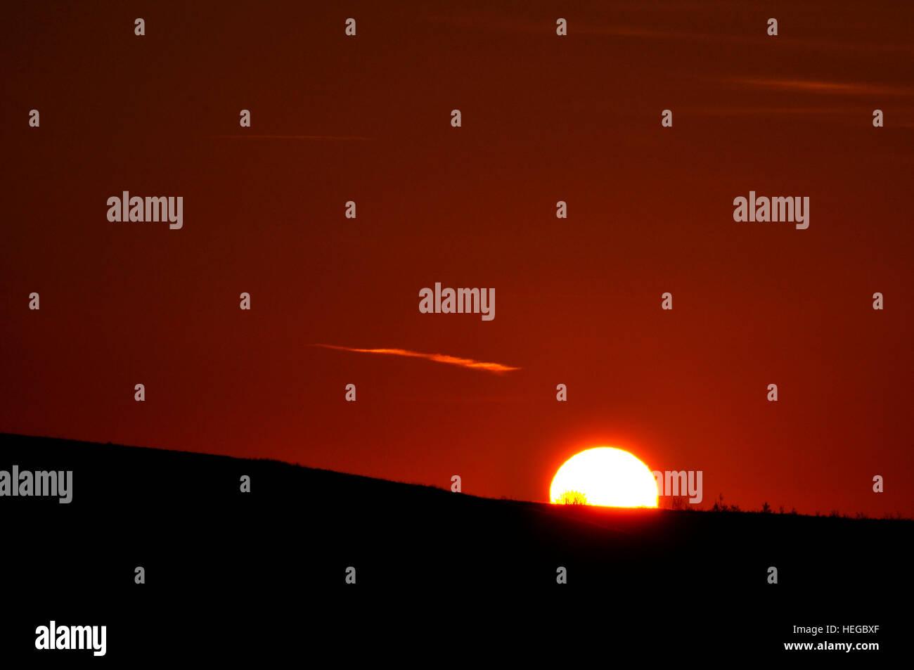Sunset sinking below the horizon - Stock Image