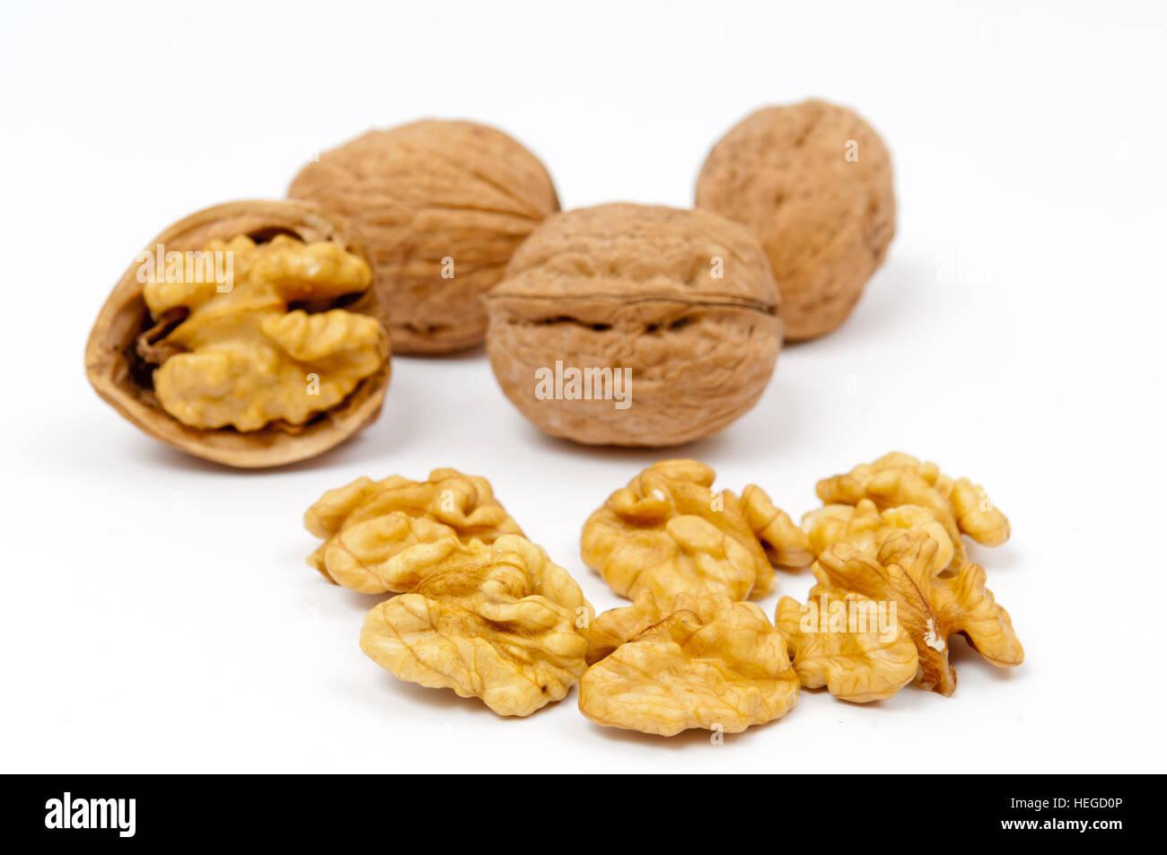 Whole walnuts and walnut kernels on white background - Stock Image