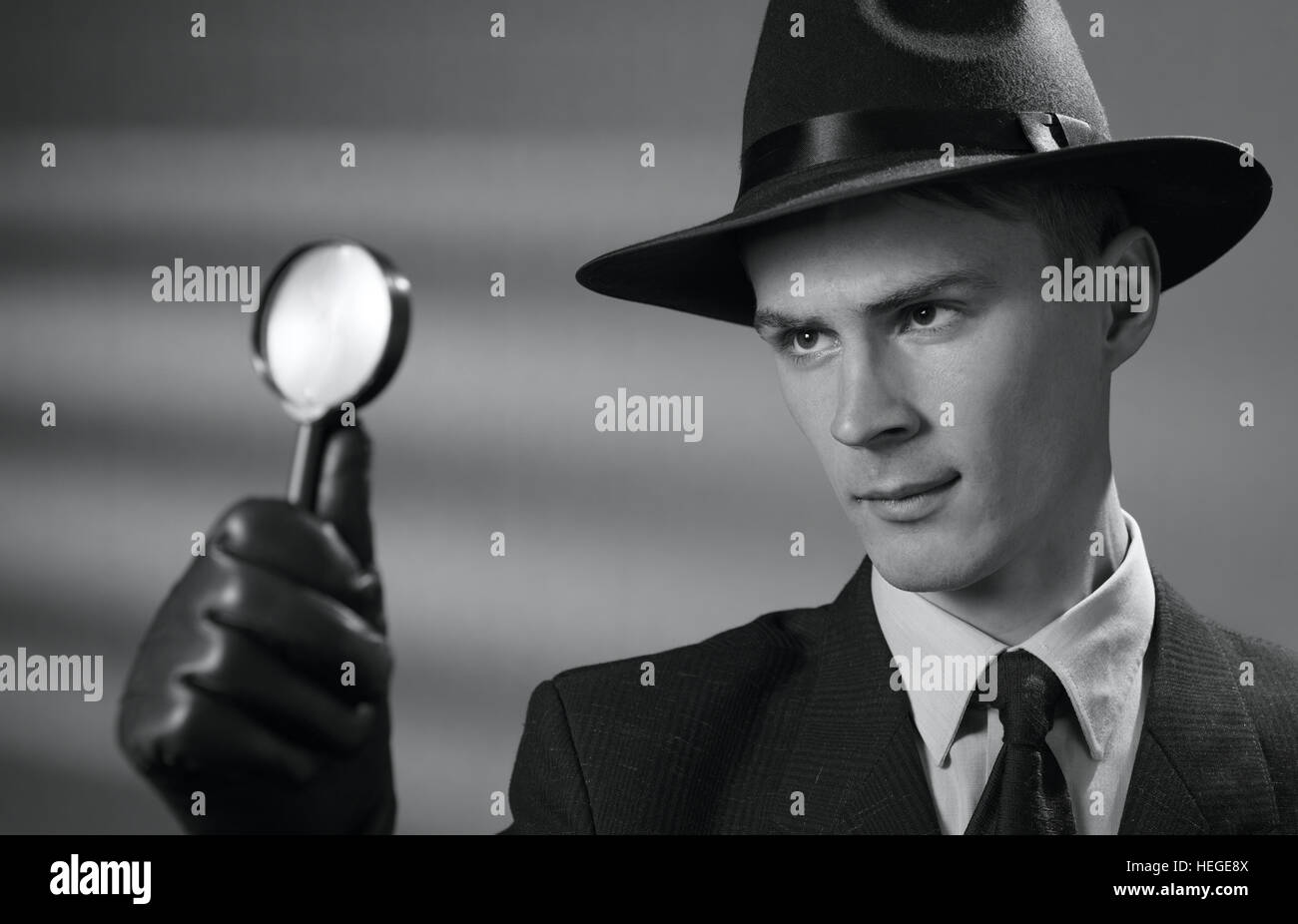 Handsome young vintage detective wearing a hat holding a magnifying glass in his gloved hand as he searches for - Stock Image