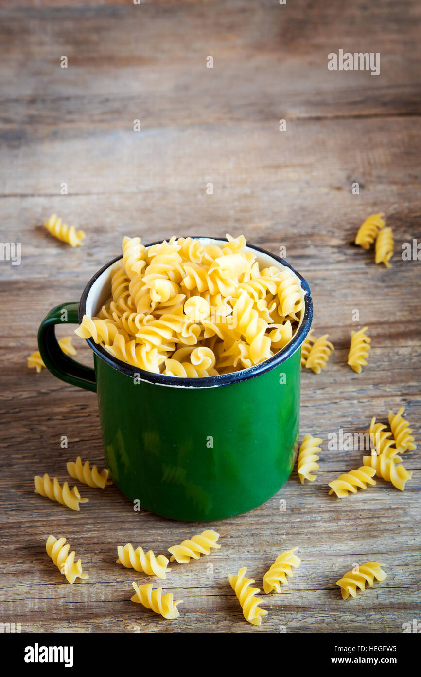 Uncooked raw italian fusilli pasta in rustic metal mug - healthy ingredient for cooking - Stock Image