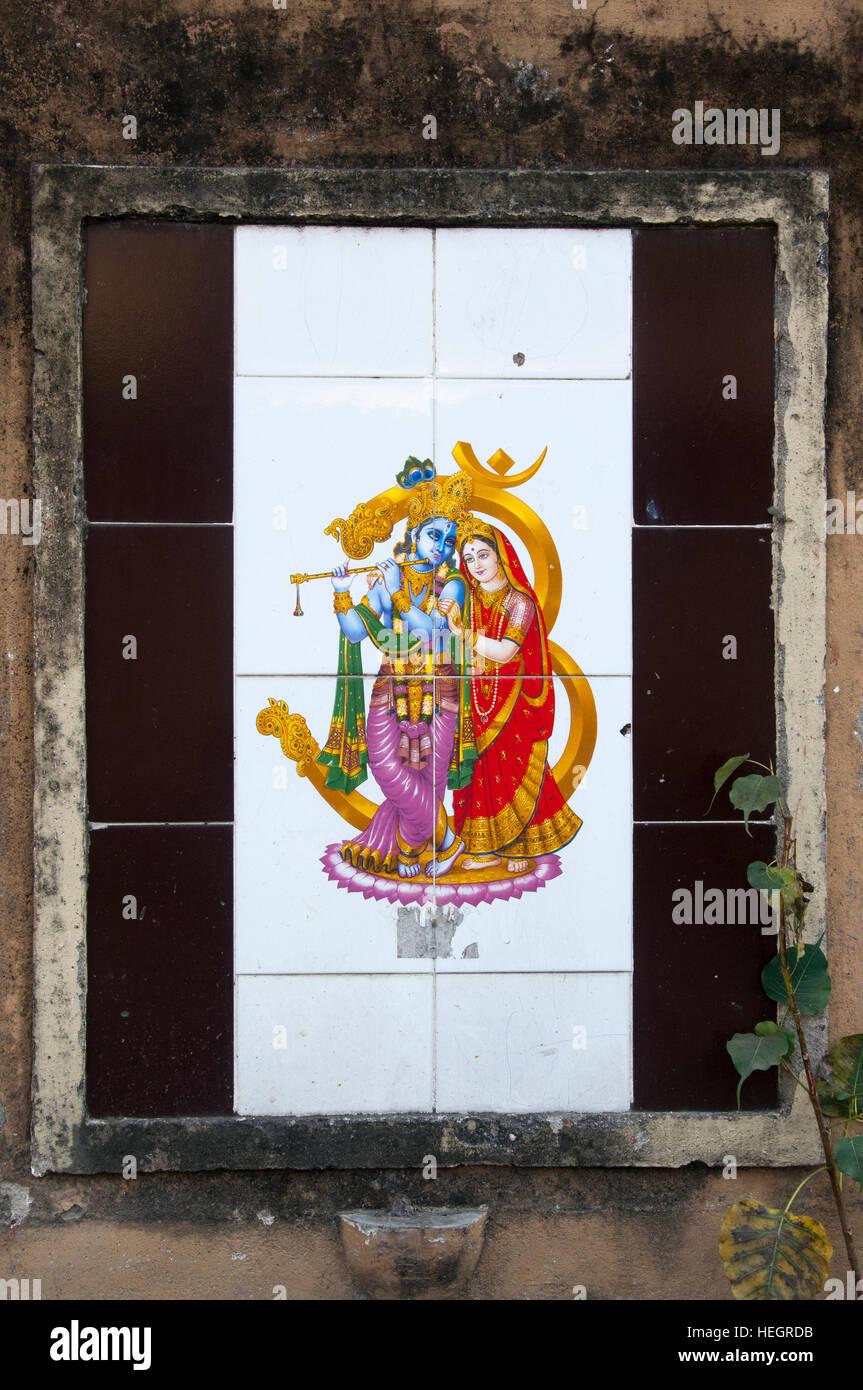 Hindu deities adorn tiled panel insert in a wall, Guwahati, Assam - Stock Image