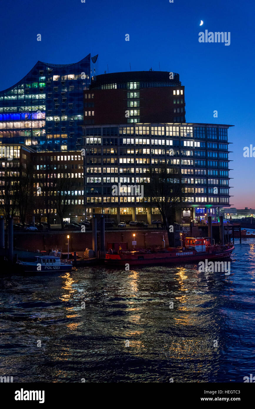 Illuminated buildings at night in HafenCity in the harbour on the Elbe river, Hamburg, Germany - Stock Image