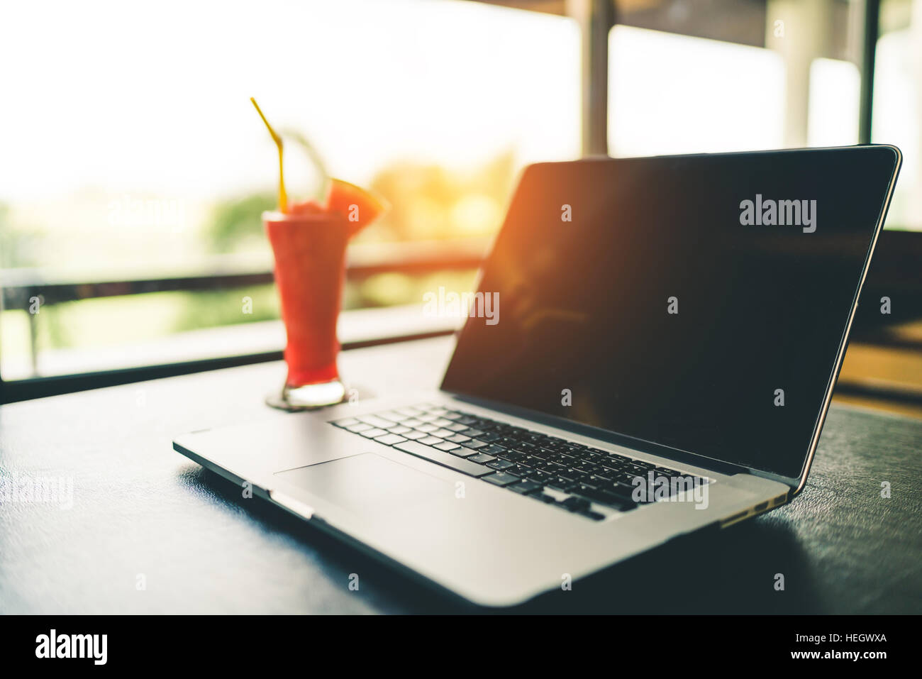 Laptop with watermelon juice on garden blur background, slow life or freelance or business travel concept, vintage Stock Photo