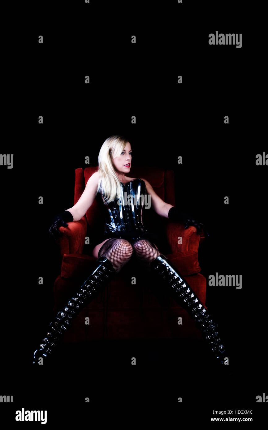 Older Caucasian Woman Sitting In Chair Black Corset Fishnet Stockings Boots Blond Hair Stock Photo