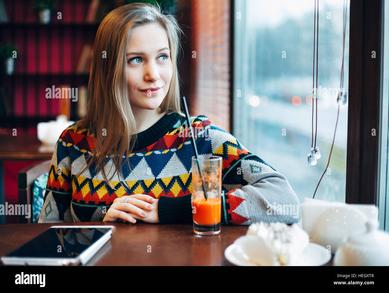 Photo of a woman drinking juice through window Stock Photo