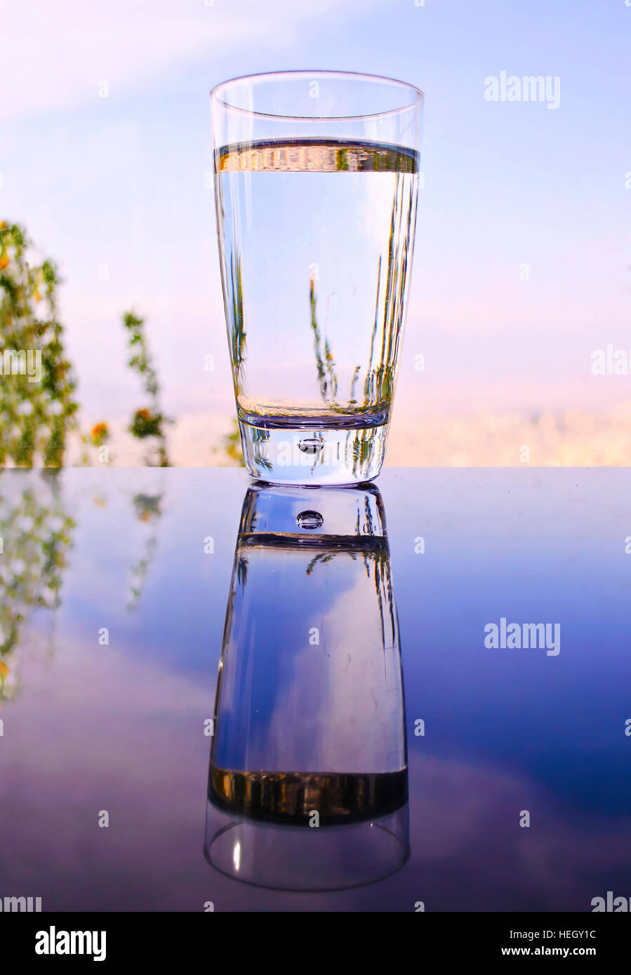 Glass With Water Reflection On Table Evening Sunset Background