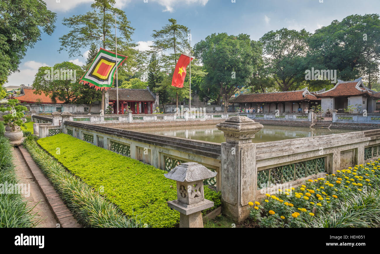 Courtyard with the pool, flags, and traditional buildings at the Temple of Literature (Van Mieu-Quoc Tu Giam), Hanoi, Stock Photo