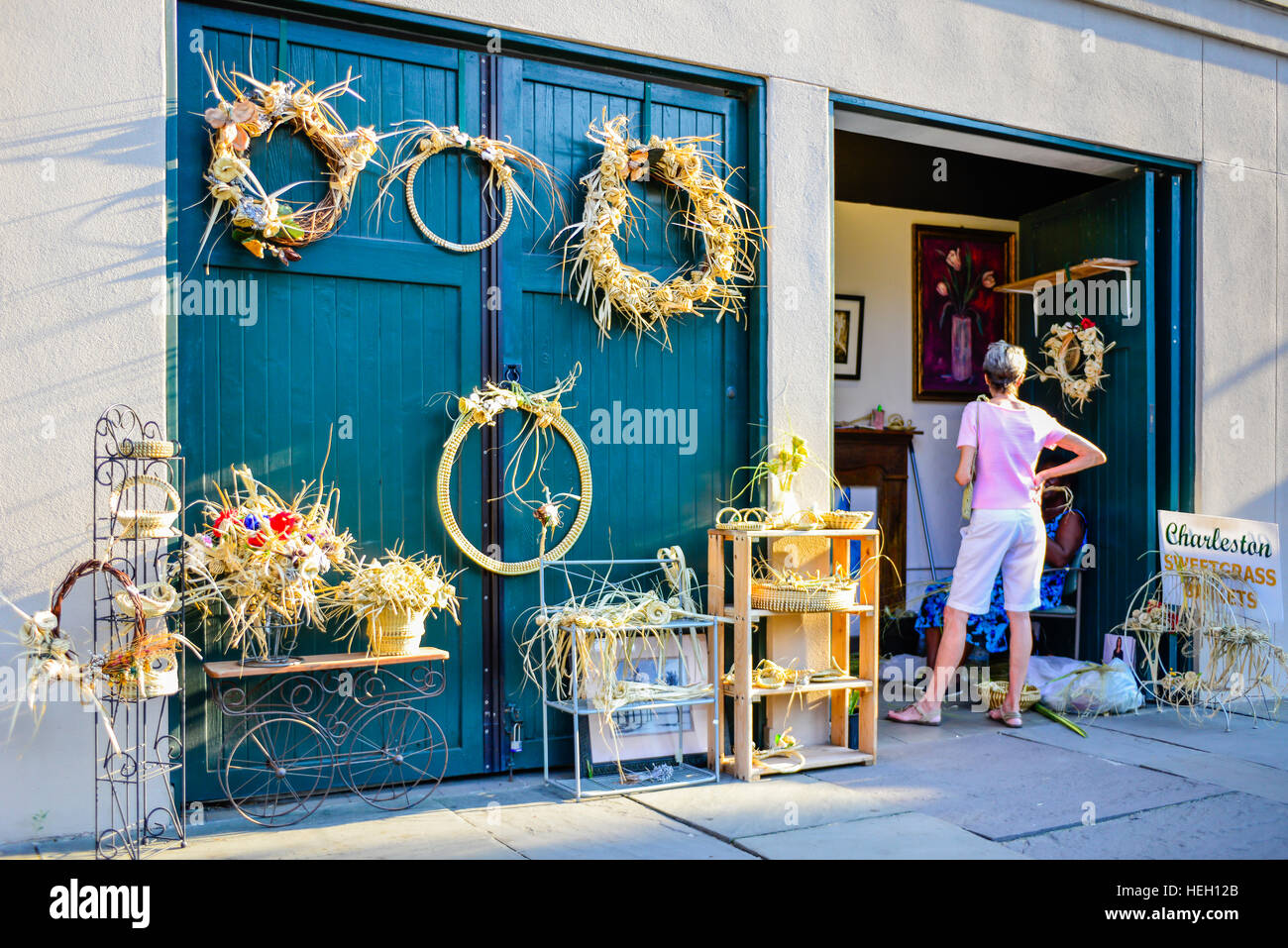 Seagrass wreaths and crafts for sell are displayed by artist outside on wooden doors in historic downtown Charleston SC & Seagrass wreaths and crafts for sell are displayed by artist outside ...