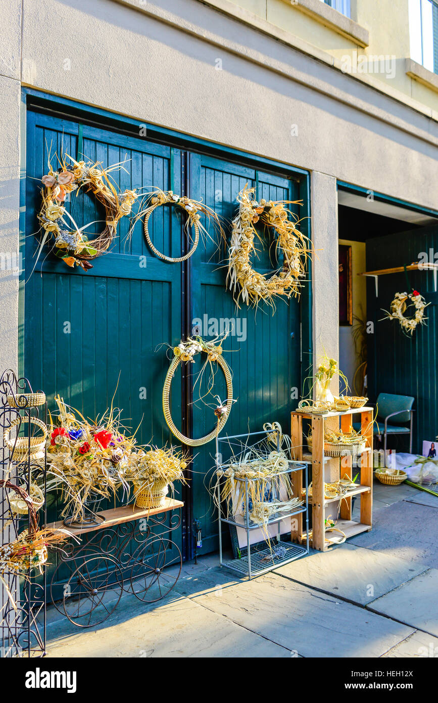 Seagrass wreaths and sea grass crafts on display by artist outside on teal green wooden doors in historic downtown Charleston SC & Seagrass wreaths and sea grass crafts on display by artist outside ...