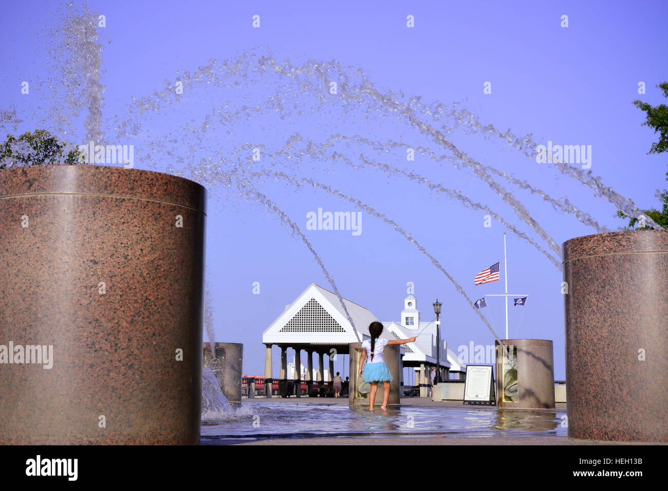 Little girl plays in water fountain in the landscaped Riverfront park along the Cooper River and Vendue Wharf in - Stock Image
