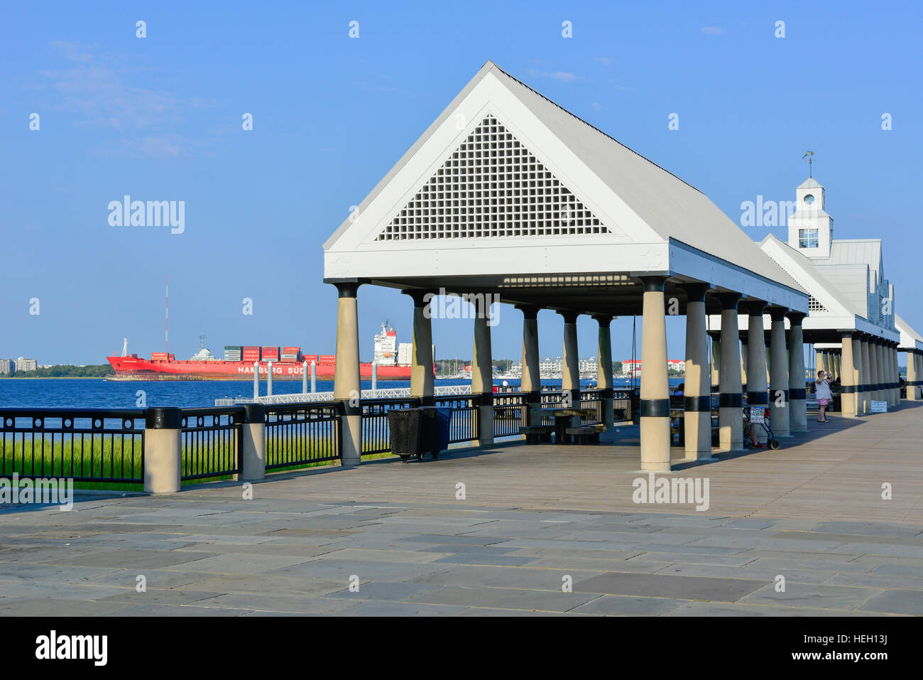 People watch container ships from Vendue Wharf at Riverfront Park covered shelters overlooking the Cooper River - Stock Image