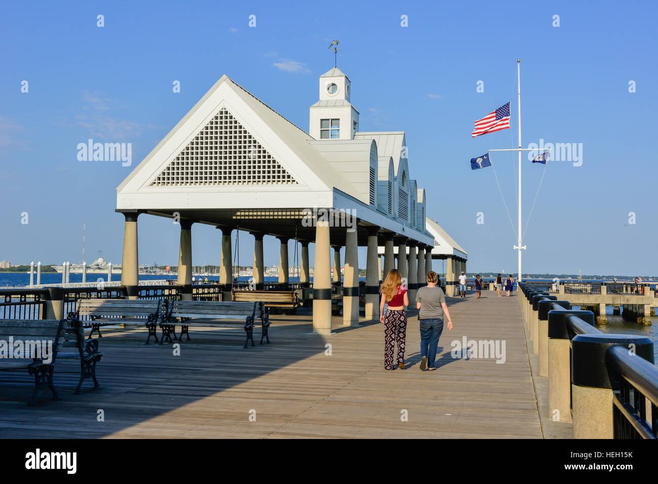People stroll Vendue Wharf at Riverfront Park near covered shelters overlooking the Cooper River in Charleston SC - Stock Image
