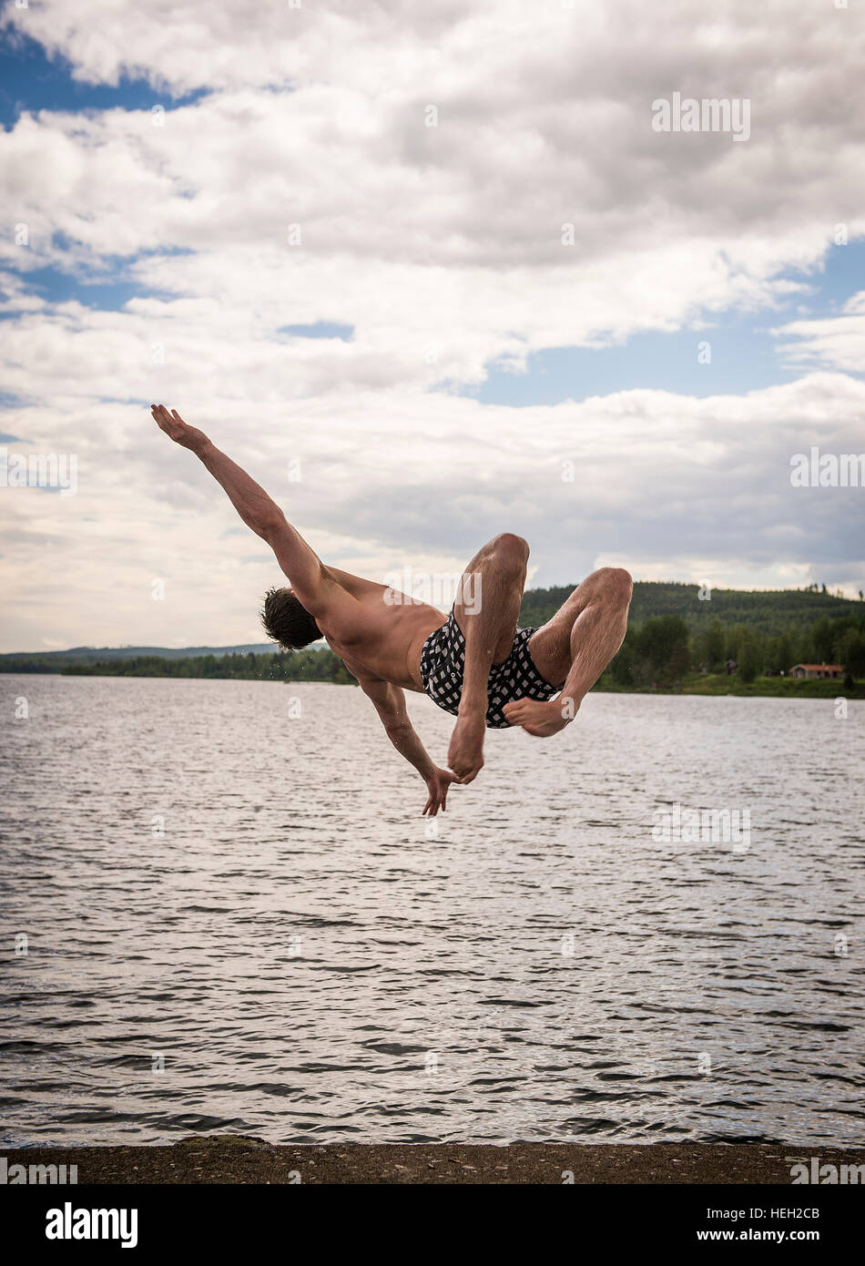 Man jumping into the water in dotted bathing shorts - Stock Image