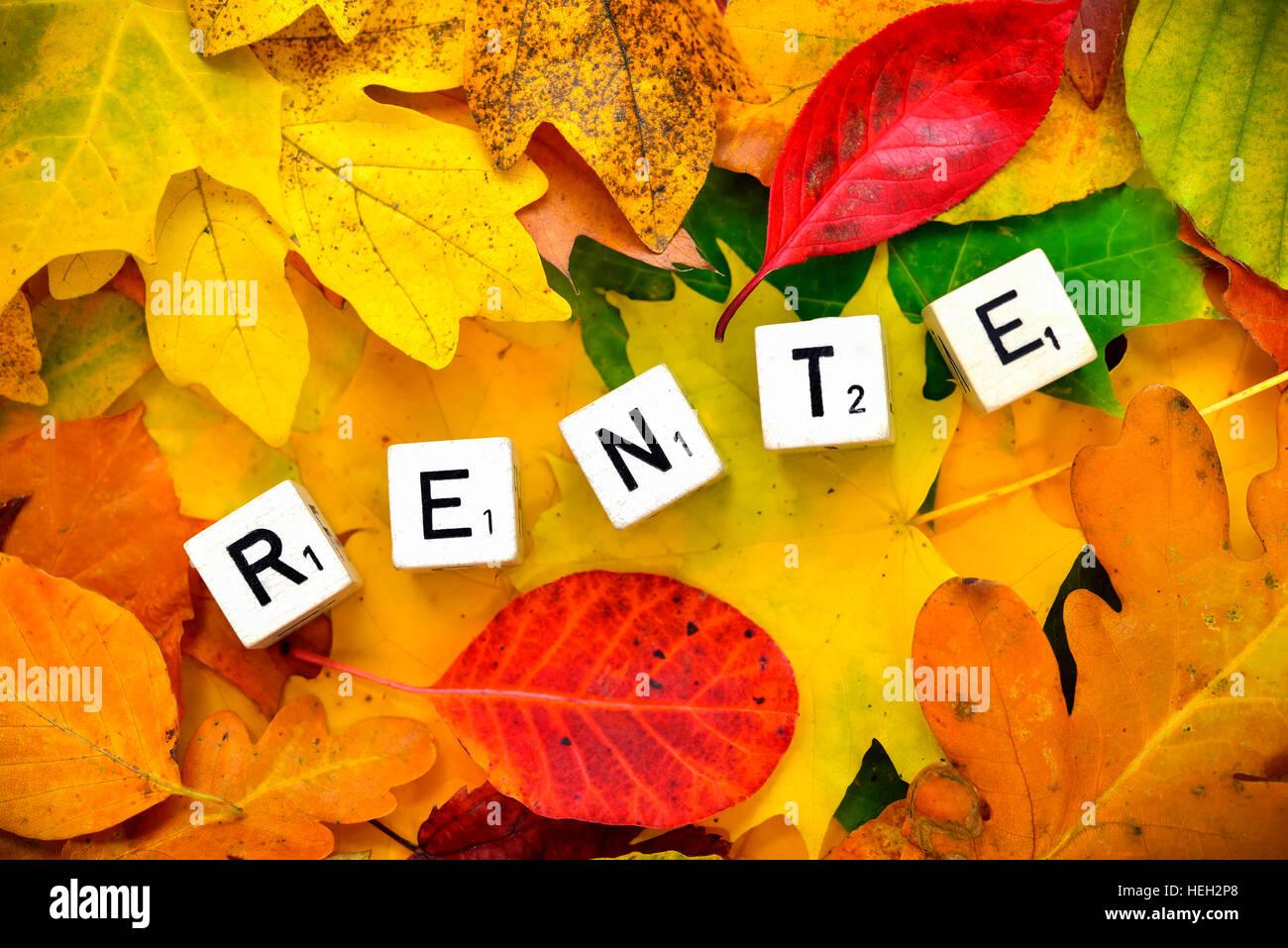 Buchstabenwuerfel bilden den Schriftzug Rente auf Herbstlaub Stock Photo
