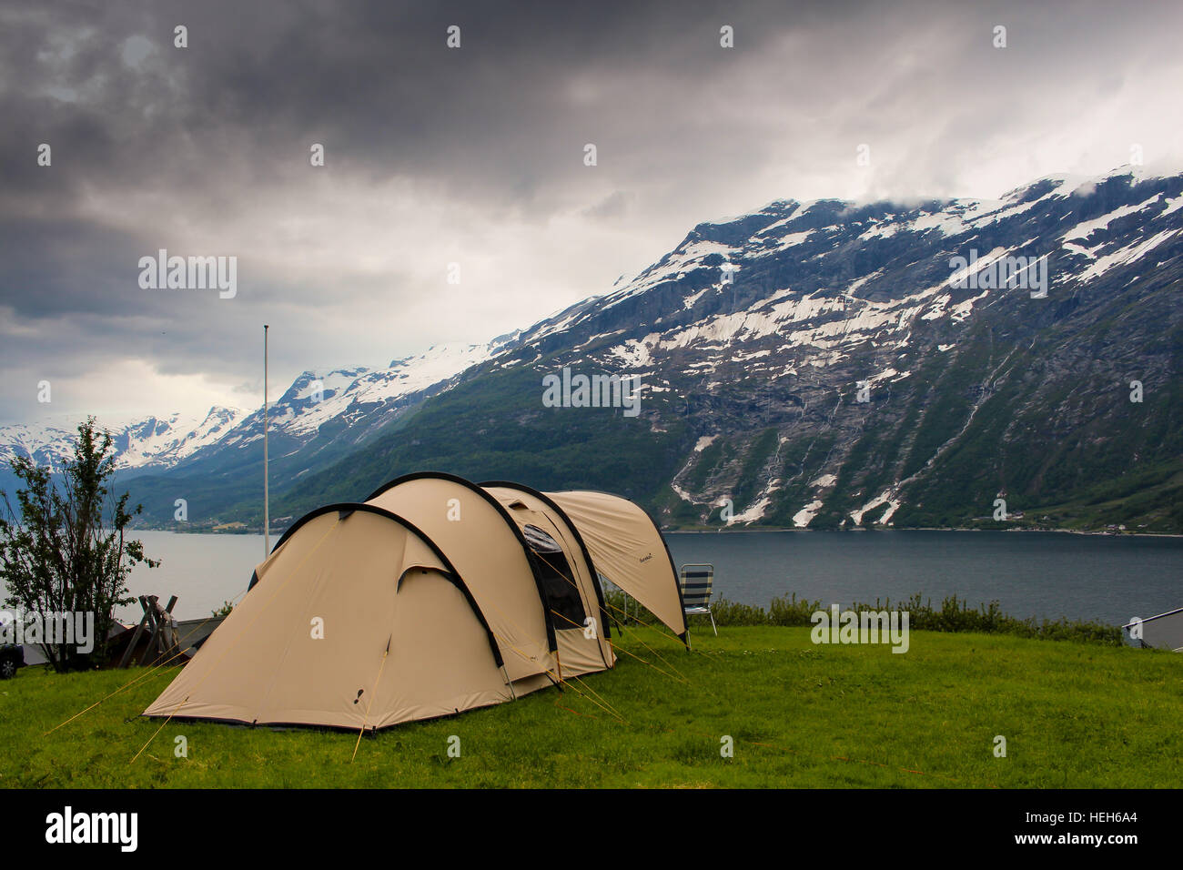 Tent camping on a Norwegian fjord with dark clouds and snow-covered mountains in the background - Stock Image