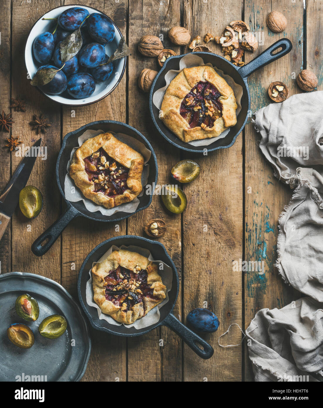 Plum and walnut crostata pie with ice-cream scoops in individual cast iron pans over rustic wooden table, top view, - Stock Image