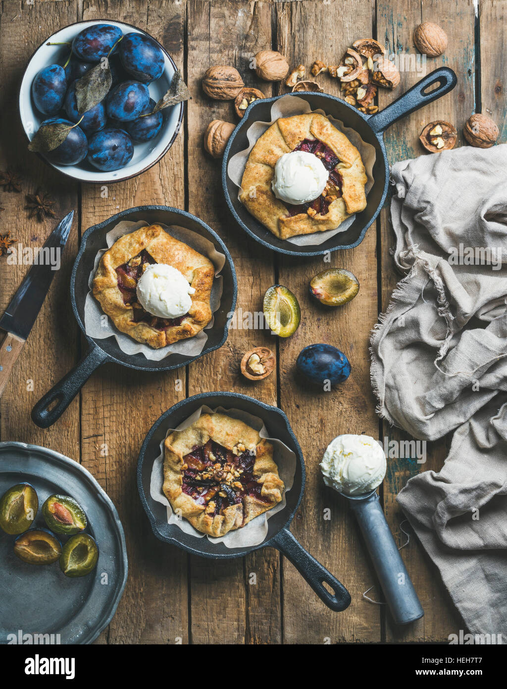 Plum and walnut crostata pie with ice-cream scoops in individual cast iron pans over rustic wooden table, top view. - Stock Image