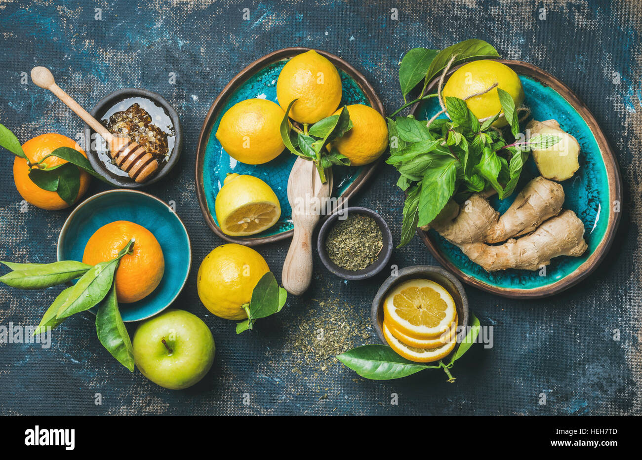 Ingredients for making natural hot drink in blue ceramic plates over dark blue shabby background, top view. Oranges, - Stock Image