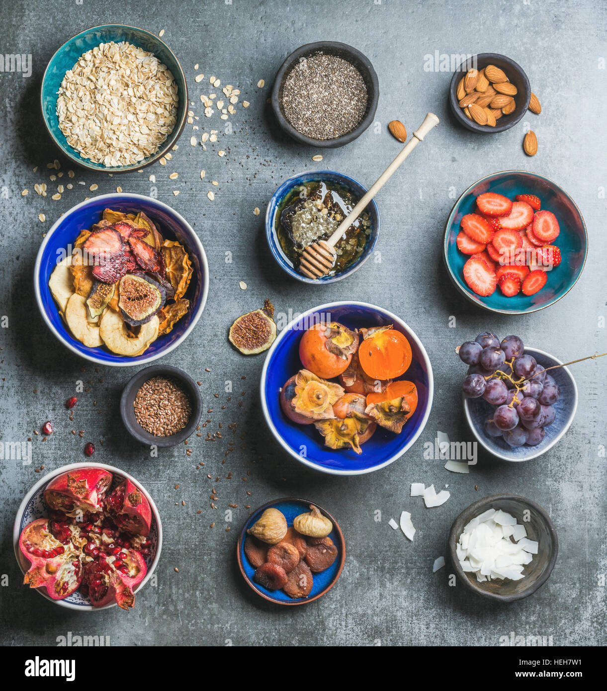 Ingredients for healthy breakfast over grey stone background, top view, square crop. Fresh and dried fruit, chia - Stock Image