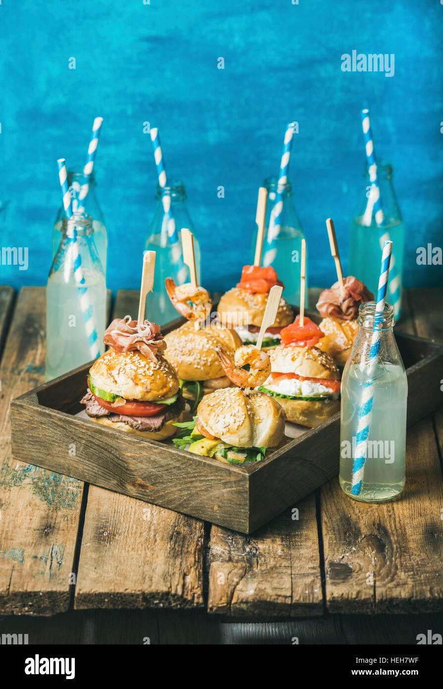 Home party food concept. Different burgers with sticks in wooden tray and lemonade in bottles with straws on rustic - Stock Image